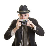 Man with a vintage film camera. A man with a startled expression holding up a vintage film camera Royalty Free Stock Photos