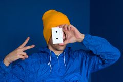 man in vintage blue jacket and yellow hat with audio tape stock photo