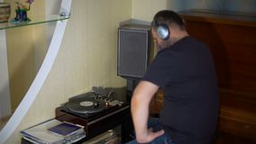 Man and vintage vynyl turntable. Male listening to vintage turntable playing vinyl record in his apartment stock video