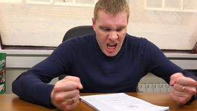 Man violently tearing paper bares his teeth and reddens his face.  stock footage
