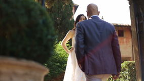 Man in violet suit walks up to beautiful brunette stock video