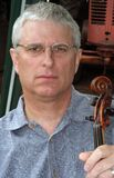 Man with Violin. Gray haired man holding old violin Royalty Free Stock Photo
