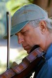 Man with Violin. Gray haired with baseball cap man playing violin Stock Image