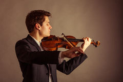 Man violinist playing violin. Classical music art. Art and artist. Young elegant man violinist fiddler playing violin on brown. Classical music. Studio shot Royalty Free Stock Photo