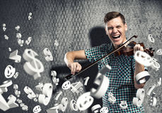 Man violinist. Young man in casual on cement background playing violin Stock Image