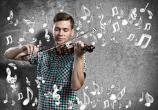 Man violinist. Young man in casual on cement background playing violin Stock Images