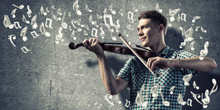 Man violinist. Young man in casual on cement background playing violin Stock Photo