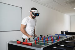 Man in virtual glasses playing at office in table soccer. Different technologies concept stock image