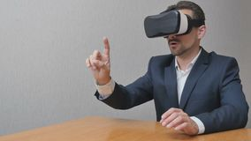 Man in virtual reality glasses. Businessman is playing online in 3d. The person uses the technology in work VR 360 Royalty Free Stock Images