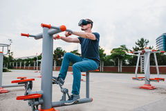 A man in virtual reality glasses is doing sports. Future technology concept. Modern imaging technology. Classes in Royalty Free Stock Photos