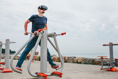 A man in virtual reality glasses is doing sports. Future technology concept. Modern imaging technology. Classes in. The man with glasses of virtual reality Royalty Free Stock Image