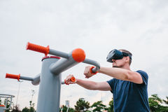 A man in virtual reality glasses is doing sports. Future technology concept. Modern imaging technology. Classes in. The man with glasses of virtual reality Stock Image