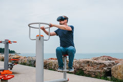 A man in virtual reality glasses is doing sports. Future technology concept. Modern imaging technology. Classes in. The man with glasses of virtual reality Royalty Free Stock Photography