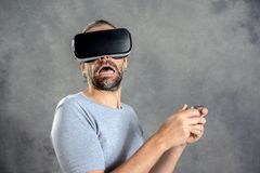 Man with virtual reality glasses looking frightened. Young man with virtual reality looking frightened Royalty Free Stock Photo