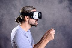 Man with virtual reality glasses playing game. Young man with virtual reality glasses playing game stock photography