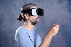 Man with virtual reality glasses playing game. Young man with virtual reality glasses playing game royalty free stock image