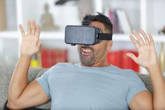 Man with virtual reality glasses playing at home stock photography