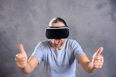 Man with virtual reality glasses playing shooting game. Young man with virtual reality glasses playing shooting game royalty free stock photos