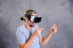 Man with virtual reality glasses playing shooting game. Young man with virtual reality glasses playing shooting game stock photos