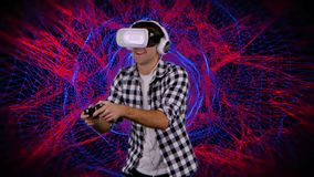 Man in virtual reality glasses plays on computer graphics background. Man in virtual reality glasses dressed in plaid shirt plays on computer graphics background stock footage