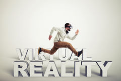 Man in virtual reality glasses running between words over white Stock Photography