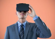 Man in virtual reality headset against orange background Royalty Free Stock Photos