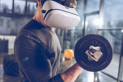 Man in virtual reality headset exercising with dumbbell in gym. Side view of man in virtual reality headset exercising with dumbbell in gym Stock Photos