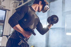 Man in virtual reality headset exercising with dumbbells in gym. Side view of man in virtual reality headset exercising with dumbbells in gym Royalty Free Stock Photography