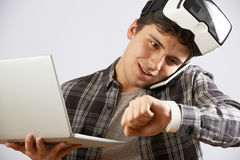 Man In Virtual Reality Headset Looking At Smart Watch And Talking On Mobile Phone royalty free stock photography