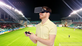 Man in virtual reality headset over football field. 3d technology, virtual reality, sport, entertainment and people concept - man with virtual reality headset or stock photo