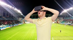 Man in virtual reality headset over football field. 3d technology, virtual reality, sport, entertainment and people concept - happy young man with virtual royalty free stock photo