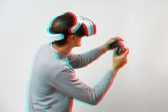 Man with virtual reality headset is playing game. Image with glitch effect. stock photos