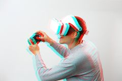 Man with virtual reality headset is playing game. Image with glitch effect. stock photo