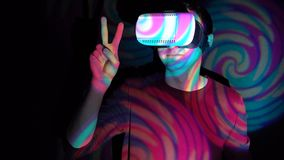 Man in virtual reality headset showing victory sign. On bright spotlight background stock footage