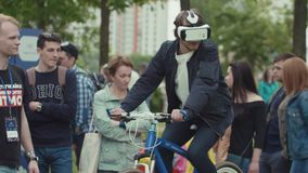 Man in virtual reality helmet riding fastened on place bicycle. Young man in virtual reality helmet riding fastened on place bicycle at crowded summer outdoor stock footage