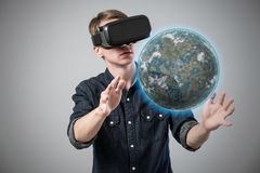Man in virtual reality. Man using virtual reality goggles on grey background Stock Photos
