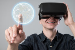 Man in virtual reality. Man using virtual reality goggles on grey background Royalty Free Stock Image