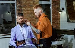 Man visiting hairstylist in barbershop. Hairdressers work for a handsome guy at the barber shop. stock photography