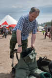 Man - visitor of show tries on the sapper suit Royalty Free Stock Photo