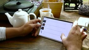 Man visits aliexpress web site using tablet pc in cafe stock footage