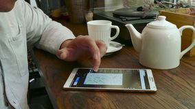 Man visits flight radar web site on tablet pc in a cafe stock video