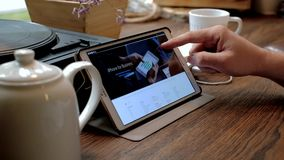 Man visits iPhone 7 website on tablet pc in a cafe stock footage