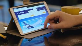 Man visits Lufthansa airlines company site site using tablet pc in cafe. Frankfurt, Germany - February 15, 2017: Man visits Lufthansa airlines company site site stock video