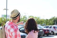 Man visningen något till kvinnan på stadsgatan mot klar himmel royaltyfria foton