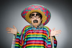 The man in vivid mexican poncho against gray Royalty Free Stock Images
