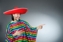 The man in a vivid mexican poncho gray background isolated Stock Photography