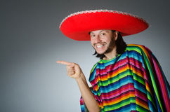 The man in a vivid mexican poncho gray background isolated Stock Photo