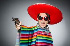 The man in vivid mexican poncho holding handgun Stock Photo