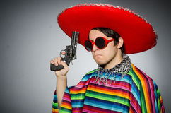 Man in vivid mexican poncho holding handgun Royalty Free Stock Photography