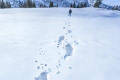 Man voetafdrukken op de sneeuw stock foto